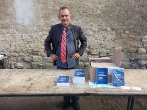 Jean-Louis Caccomo à son stand se prépare à présenter son dernier livre dans une conférence qui se déroulera sous peu dans une des salles du Château.